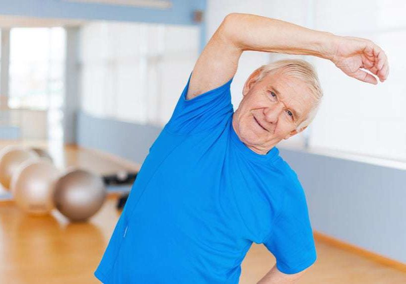 33695915 - active senior man. cheerful senior man doing stretching exercises and smiling while standing indoors